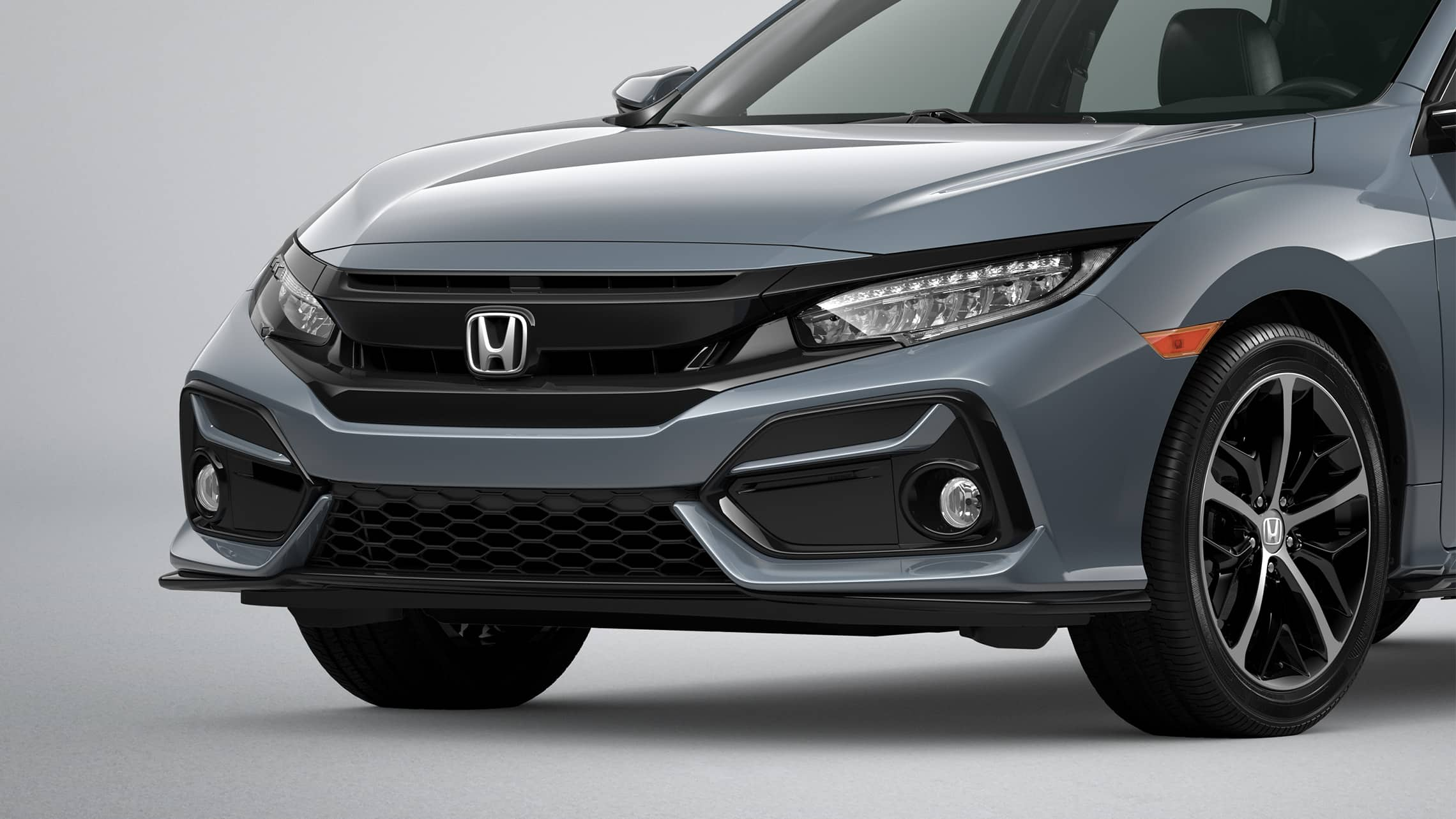 Front driver-side close-up view of the 2021 Honda Civic Sport Touring Hatchback in Sonic Gray Pearl.