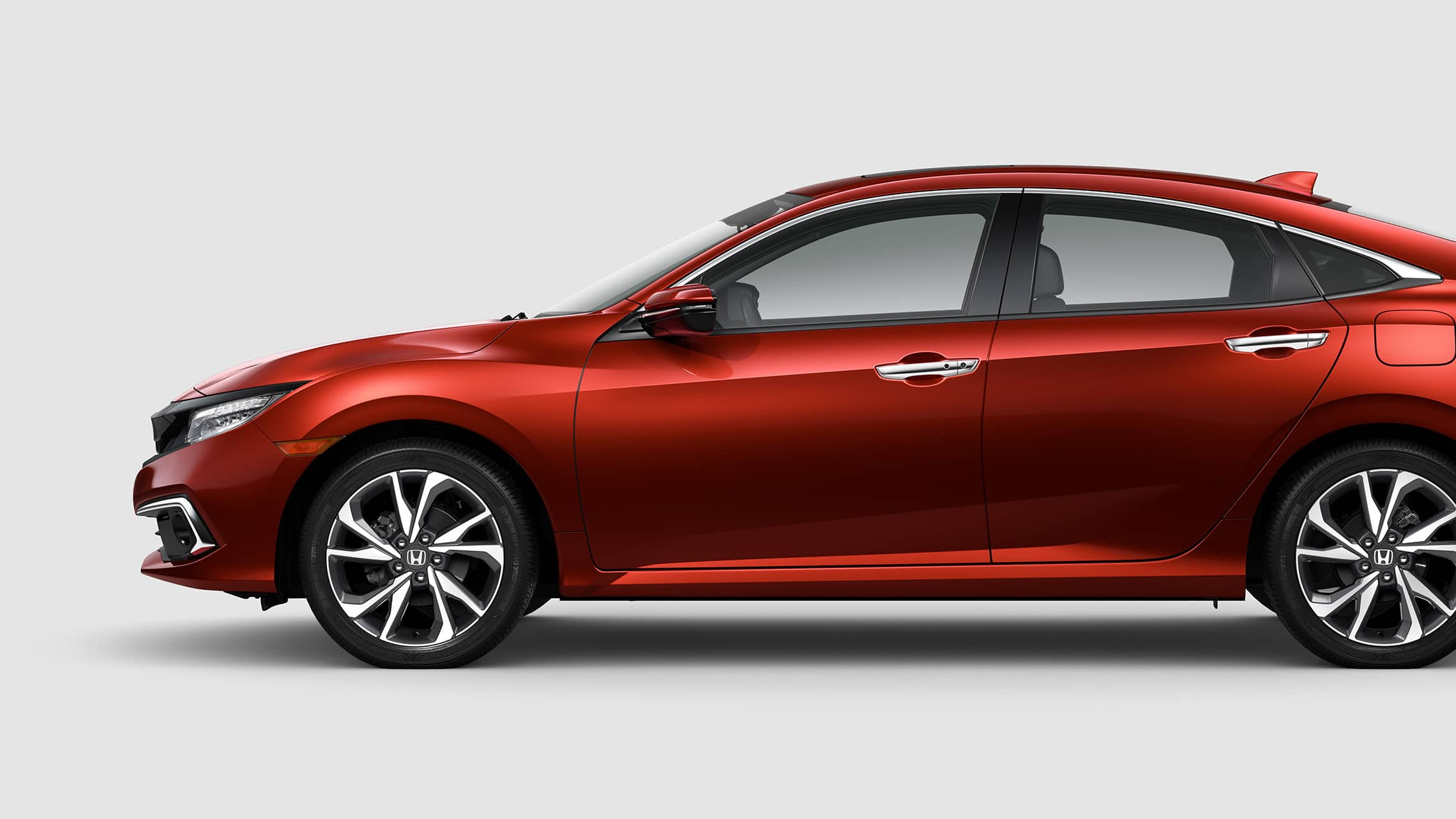 Driver-side profile view of the 2021 Honda Civic Touring Sedan in Molten Lava Pearl.