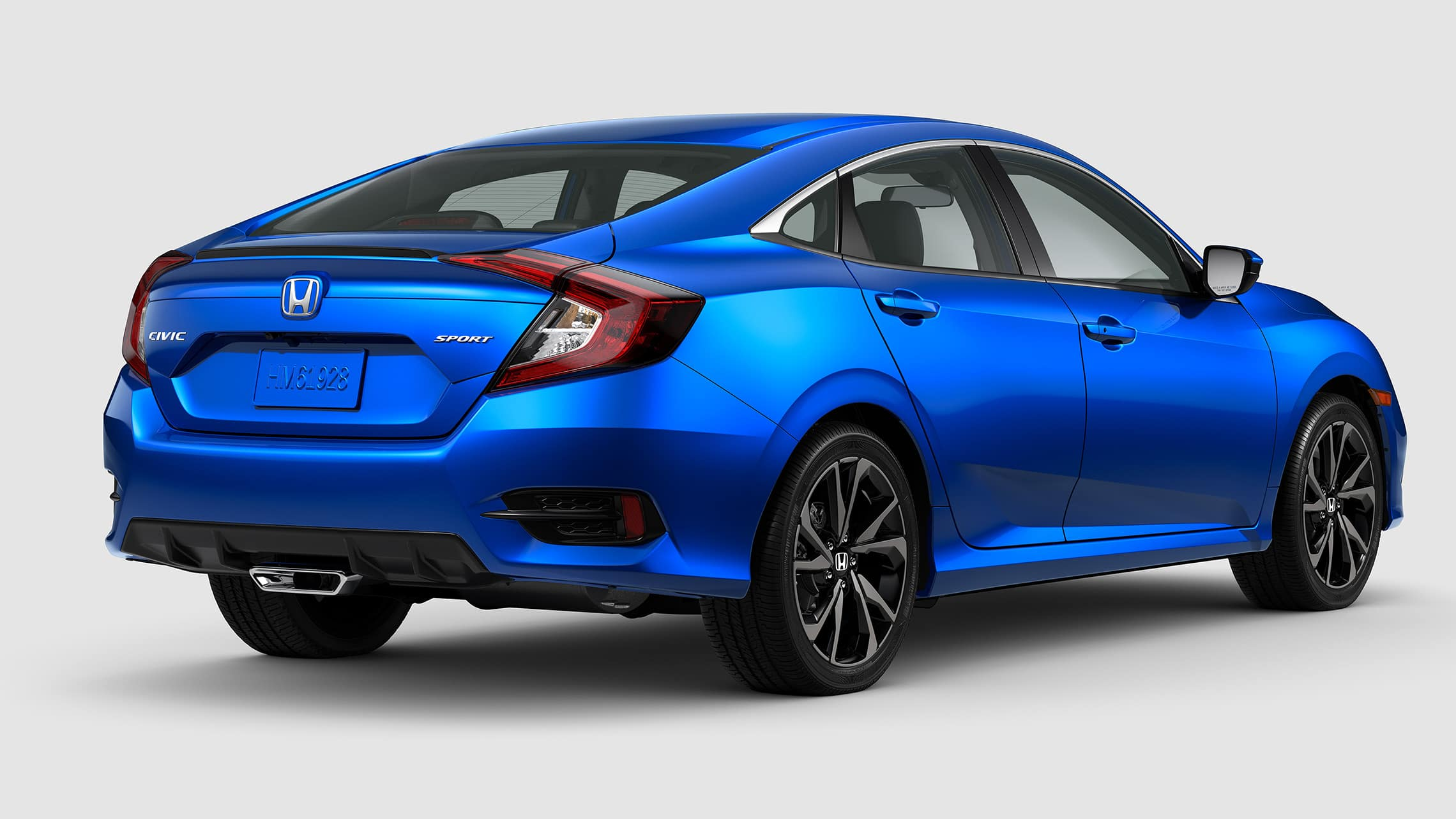 Rear passenger-side view of the 2021 Honda Civic Sport Sedan in Aegean Blue Metallic.